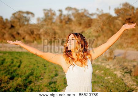 Beautiful young woman walking in the countryside with beautiful light
