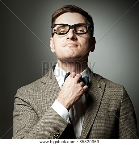 Confident nerd in eyeglasses adjusting his bow-tie against grey background
