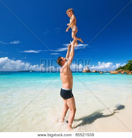 Two year old baby boy and his father playing on beach at Seychelles