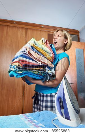 Housewife With Big Stack Of Towels For Ironing