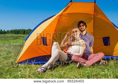 Outdoor Portrait Of A Happy Couple In Love Near The Tent On The Green Grass
