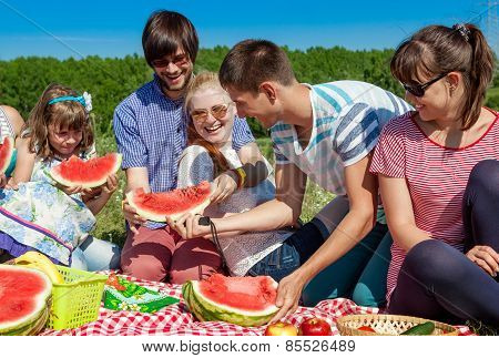Outdoor Group Portrait Of Happy Company Having Picnic On Green Grass In Park And Enjoying Watermelon