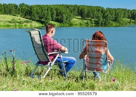 Outdoor Portrait Of Happy Couples At The Lake, Sitting In A Chair