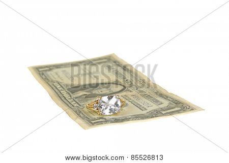 Ring on a $1 bill representing the high cost of weddings, isolated on white