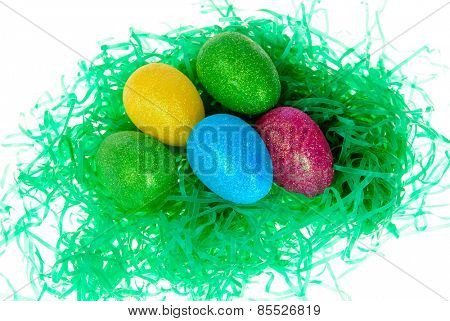 colorful sparkling Easter eggs in a nest of green, isolated on white