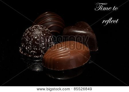 Low Key lighting on a selection of premium chocolates, sitting on a reflective background with space for text