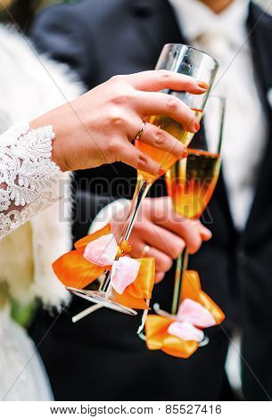 Hands Of Bride And Groom With Glasses Of Champagne