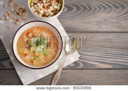 Pea soup with parmesan on wooden background.