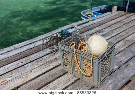 Box with fishing equipment at jetty on tropical coast