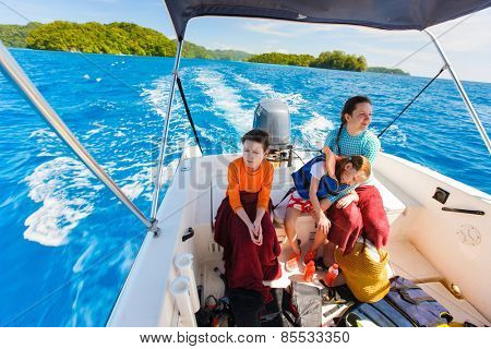 Family of mother and her kids at small boat on private water tour or excursion