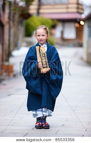 Little girl wearing yukata traditional Japanese kimono at street of a onsen resort town in Japan. Translation of the text on wooden plate: passport for round bath visit to protect you from bad luck.