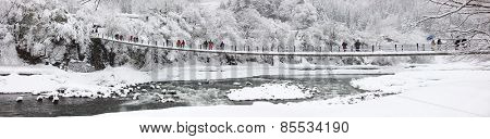 People crossing the bridge over Shogawa river at historic Japanese village Shirakawa-go at winter, one of Japan's UNESCO world heritage sites