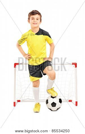 Full length portrait of a junior soccer player standing in front of a small goal isolated on white background