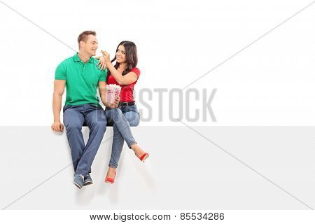 Woman feeding popcorn to her boyfriend seated on a panel isolated on white background