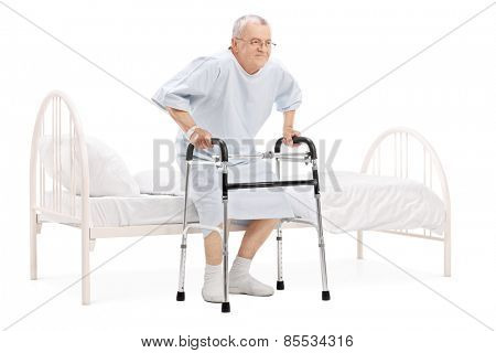 Mature patient getting up from bed with walker isolated on white background