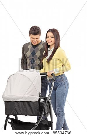 Vertical shot of young parents pushing a baby stroller isolated on white background