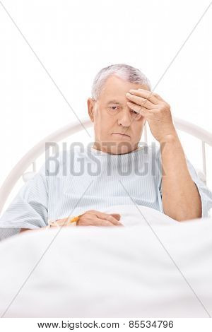 Mature patient having a headache and lying in a hospital bed isolated on white background