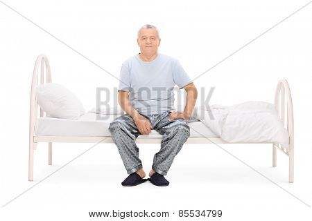 Senior man in pajamas sitting on a bed isolated on white background
