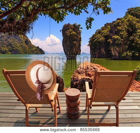 Exotic rest in Thailand. The coast of the gulf in the Andaman Sea. Two convenient chaise lounges and an elegant hat on one