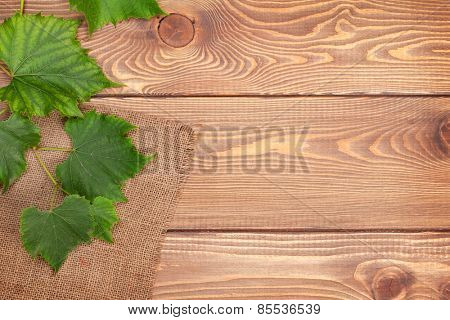 Grape vine over wooden table background with copy space