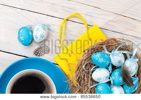 Easter background with blue and white eggs in nest, yellow tulips and coffee cup over white wood. Top view
