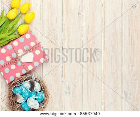 Easter background with blue and white eggs in nest, yellow tulips and gift box. Top view with copy space. Vintage toned