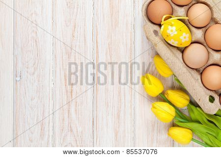 Easter background with eggs and yellow tulips over white wood. Top view with copy space