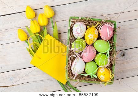 Easter background with colorful eggs and yellow tulips over white wood. Top view