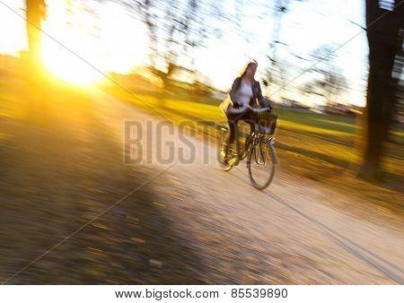 Woman Cycling At Sunset.
