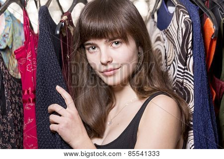 Portrait Of A Beautiful Teenage Girl In Front Of Some Dresses
