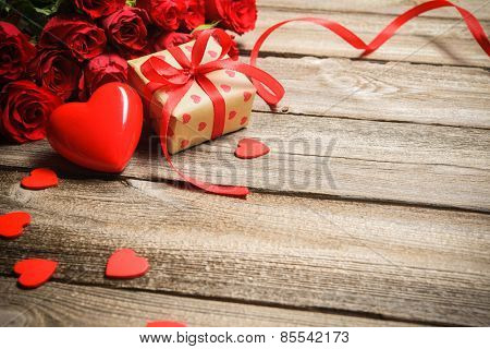 Bunch of roses with a gift box and red heart on wooden background