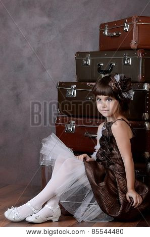 The little girl with old retro suitcases