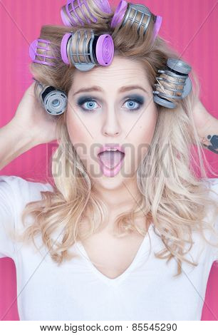 Young attractive surprised blonde woman with hot rollers beauty concept