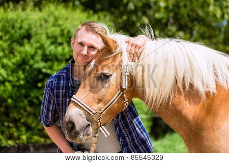 Man petting horse on pony farm