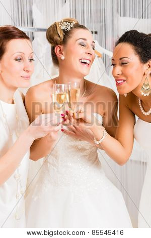 Women drinking champagne while bridal gown fitting in wedding fashion store