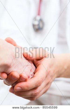 Doctor giving pensioner in surgery comfort and consoling with holding hands