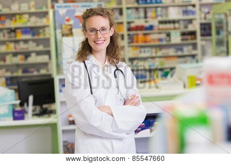 Phamacist in lab coat with stethoscope and arms crossed in the pharmacy