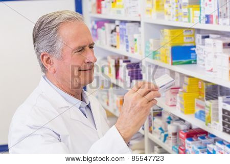 Senior pharmacist taking medicine from shelf at the hospital pharmacy