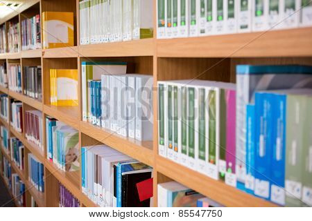 Volumes of books on bookshelf in library at the university