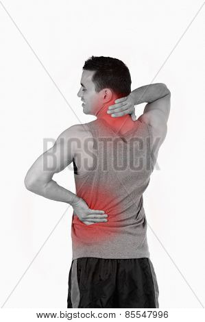 Portrait of a sports man having a back pain against a white background
