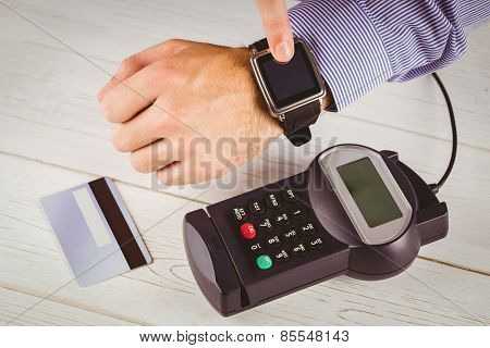 Man using smart watch to express pay on a wooden table