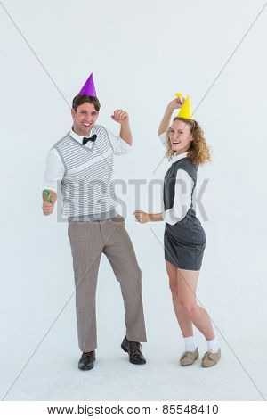 Geeky couple dancing with party hat on white background