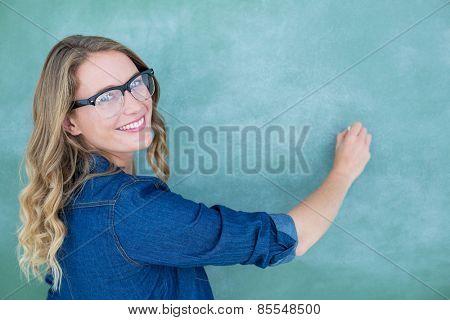 Smiling geeky teacher writing on blackboard in classroom