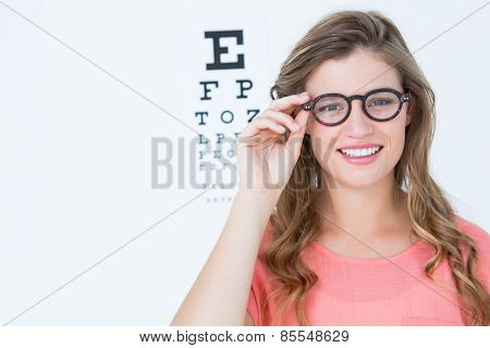 Pretty geeky hipster with glasses and eye test on white background