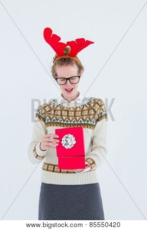 Surprised geeky hipster opening present on white background