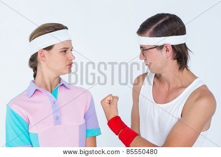 Geeky hipster showing fist to his girlfriend on white background
