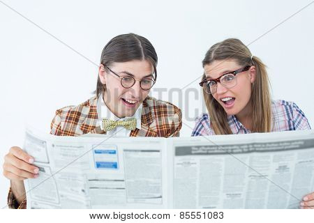 Geeky hipsters reading the newspaper on white background