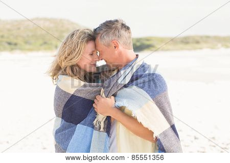 Happy couple wrapped up in blanket at the beach