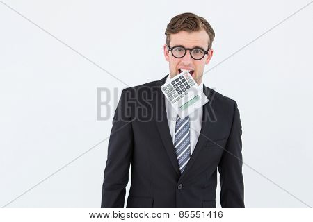 Geeky businessman biting calculator on white background