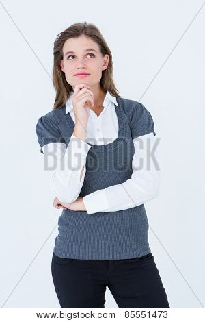 Thoughtful blonde woman with hand on chin on white background
